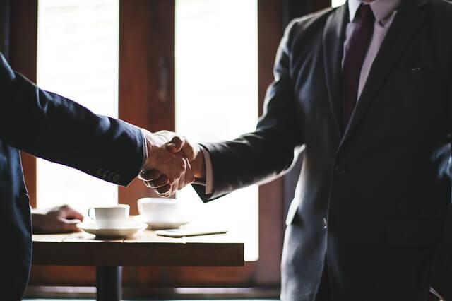就職エージェントと握手をしている